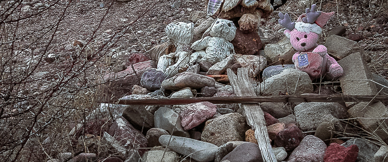 Stone cairn bedecked with weathered stuffed animals.