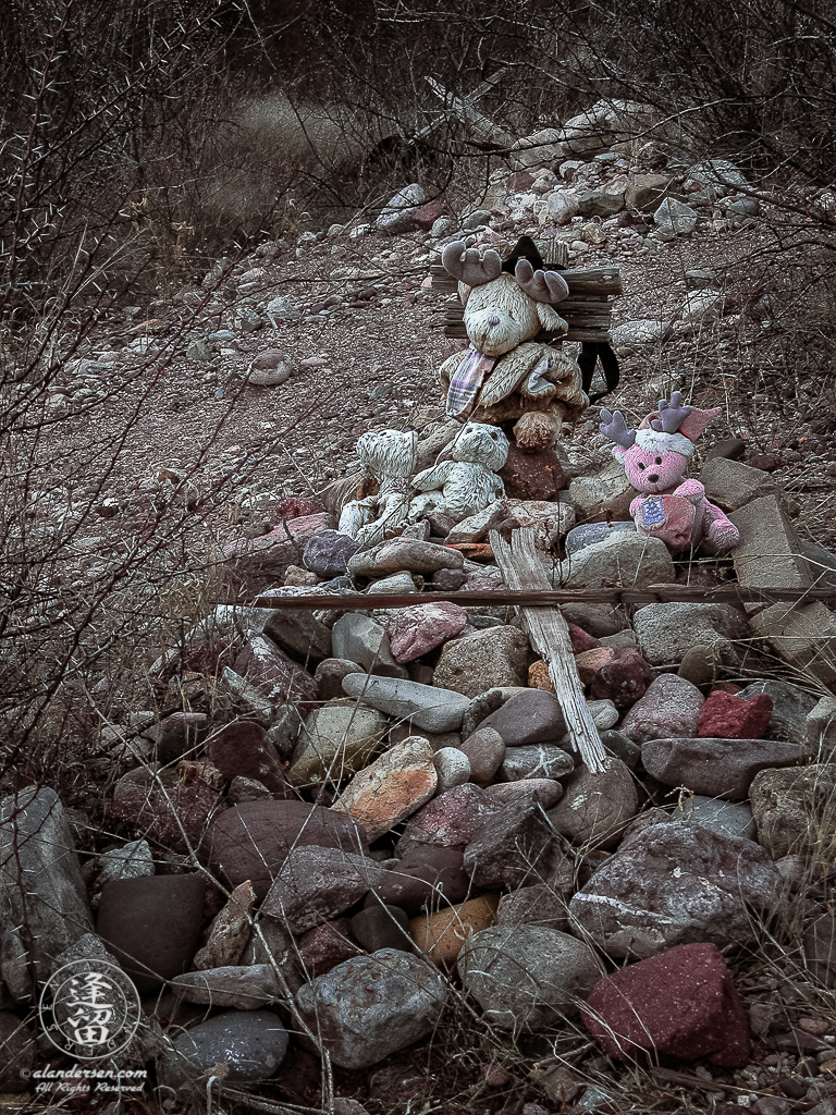 A stone cairn, bedecked with weathered stuffed animals and two termite-chewn pieces of wood arranged in the symbol of the cross, denoting the final burial places of the residents of Fairbank, an old ghost town in Southeastern Arizona.