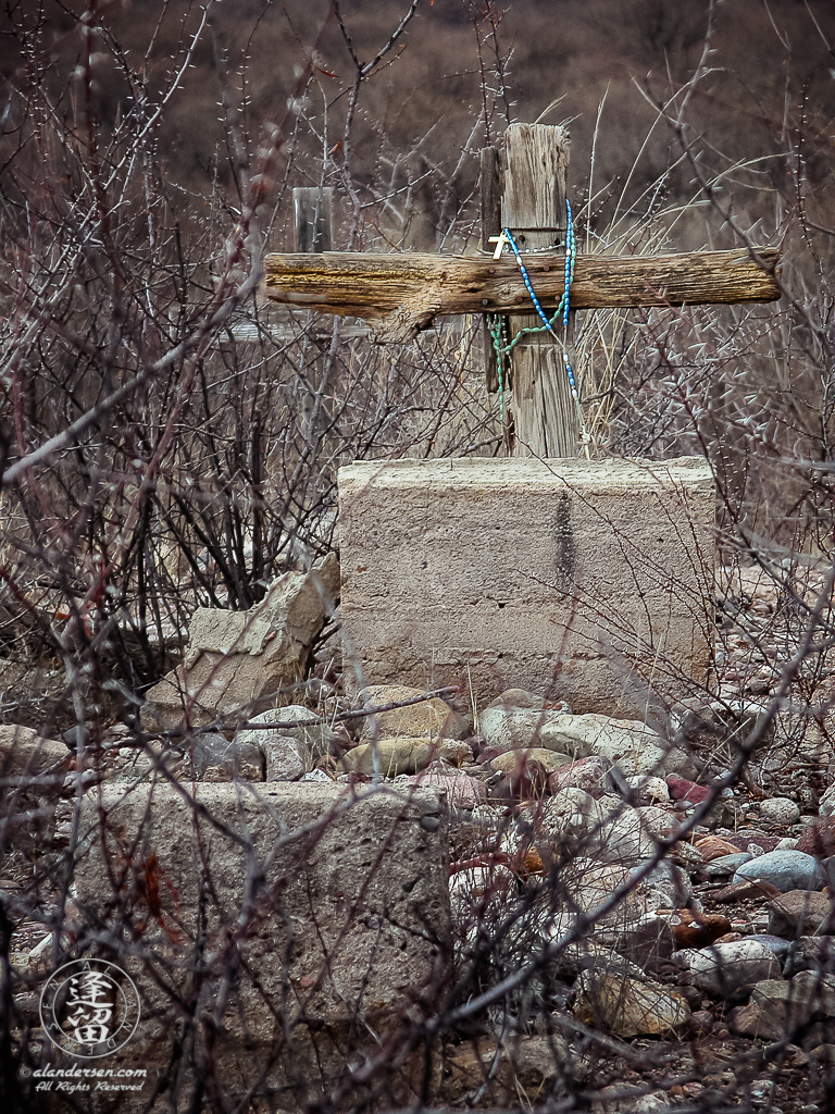 Wooden cross grave marker draped with torquoise rosary.