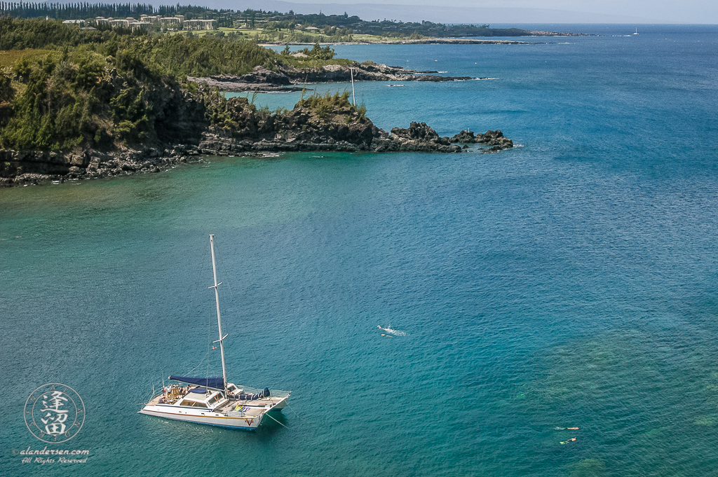 Catamaran anchored in the clear blue waters of Honolua Bay on Hawaiian Island of Maui.
