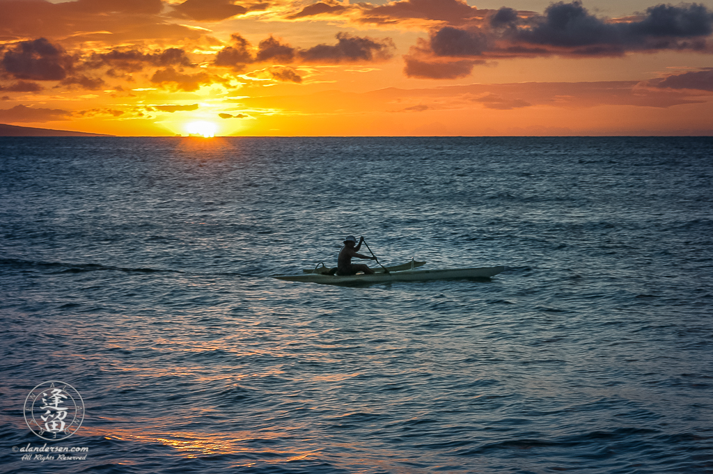 Canoer paddling along the Kaanapali coast at sunset.