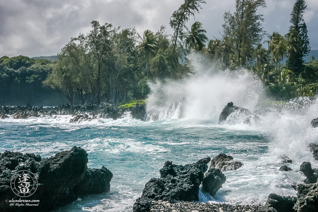 Waves crashing against black lava rocks at Ke'anae Peninsula.