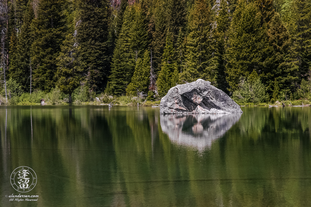 Boulder and tree reflections in String Lake at Grand Teton National Park in Wyoming.