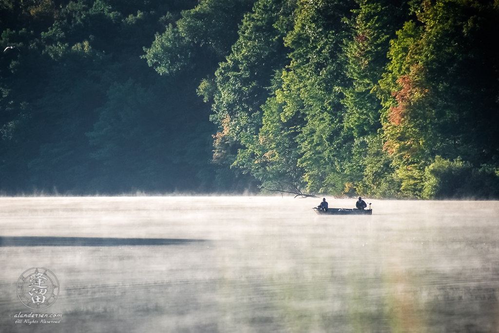 Two anglers out fishing in boat on misty Hudson Lake.