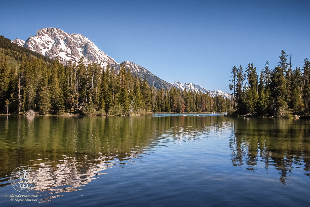 Snow-covered slopes of Mt. Moran reflected in String Lake at Grand Teton National Park.