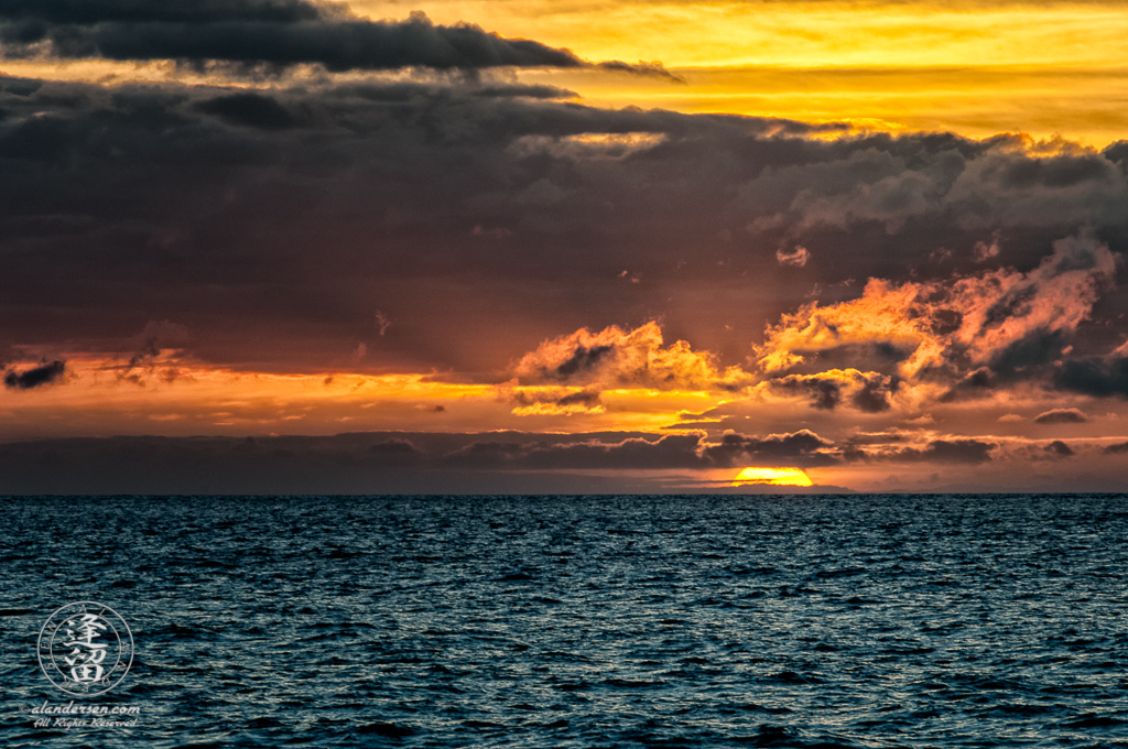 Golden sun dipping below dark ocean horizon at sunset.