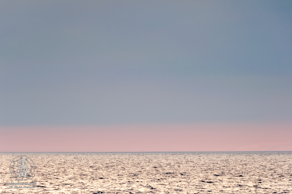 Pastel pink and blue evening sky merging into gray waters of the ocean at the horizon.