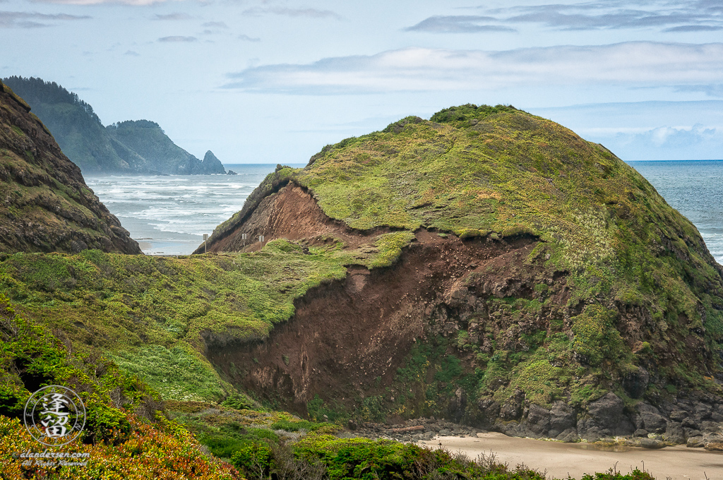 A round grass-covered hill succumbs to the process of erosion just off of Hwy 101 on a late hazy morning along the Oregon coast near Rock Creek.