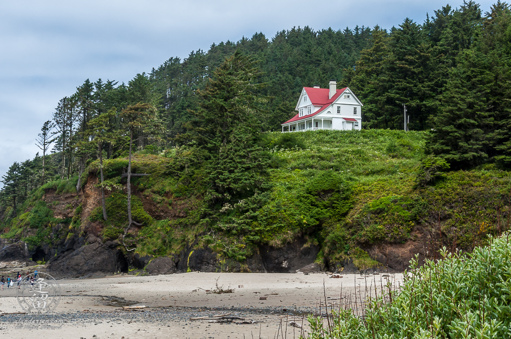 Red-roofed white two-story home of the Hecata Head lighthouse keeper.