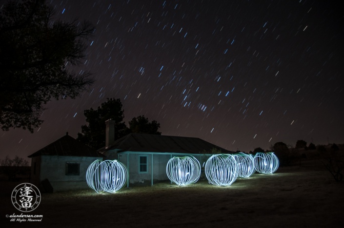 Orion rising over Brown Canyon Ranch House with floating spheres of light.