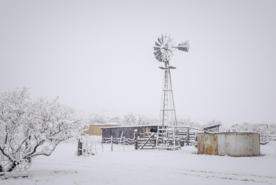 Thick snow blanketing windmill and corrals