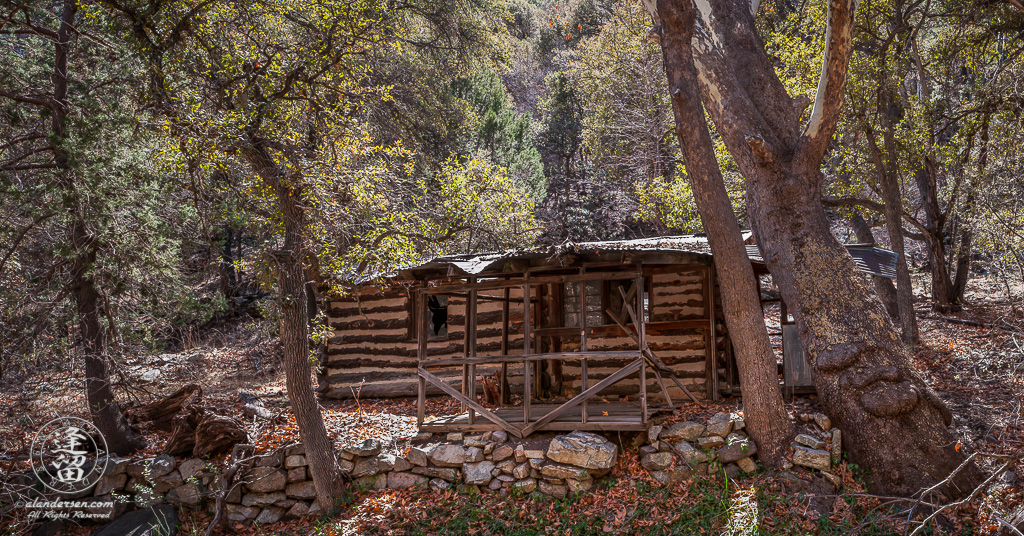 Deserted old log cabin next to creek.