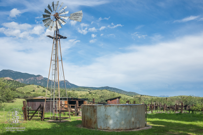 Windmill, corrals, and rolling grassy hills.