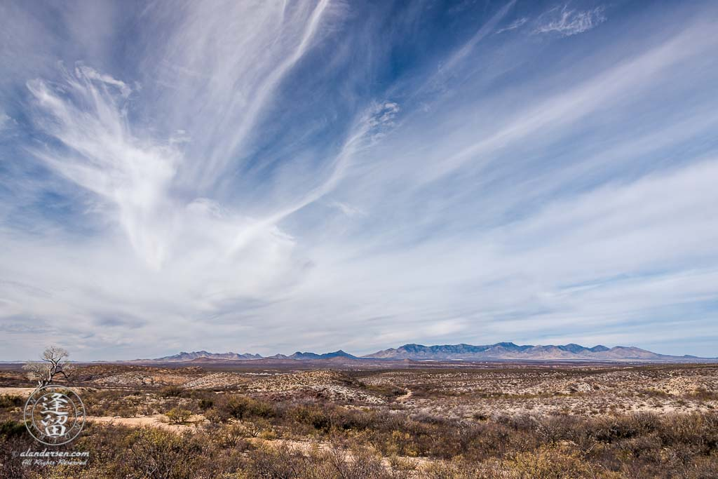 Cirrus clouds streaking over desert mountain range.