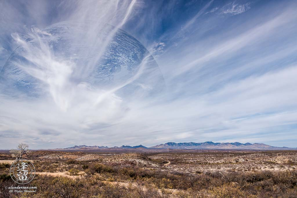 A digital composite of desert landscape with large planet in blue sky streaked by white wispy cirrus clouds.