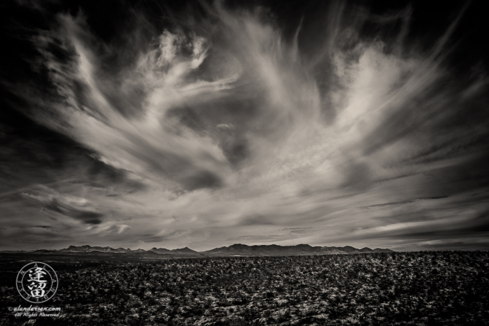 Cirrus clouds streaking over desert mountain range.
