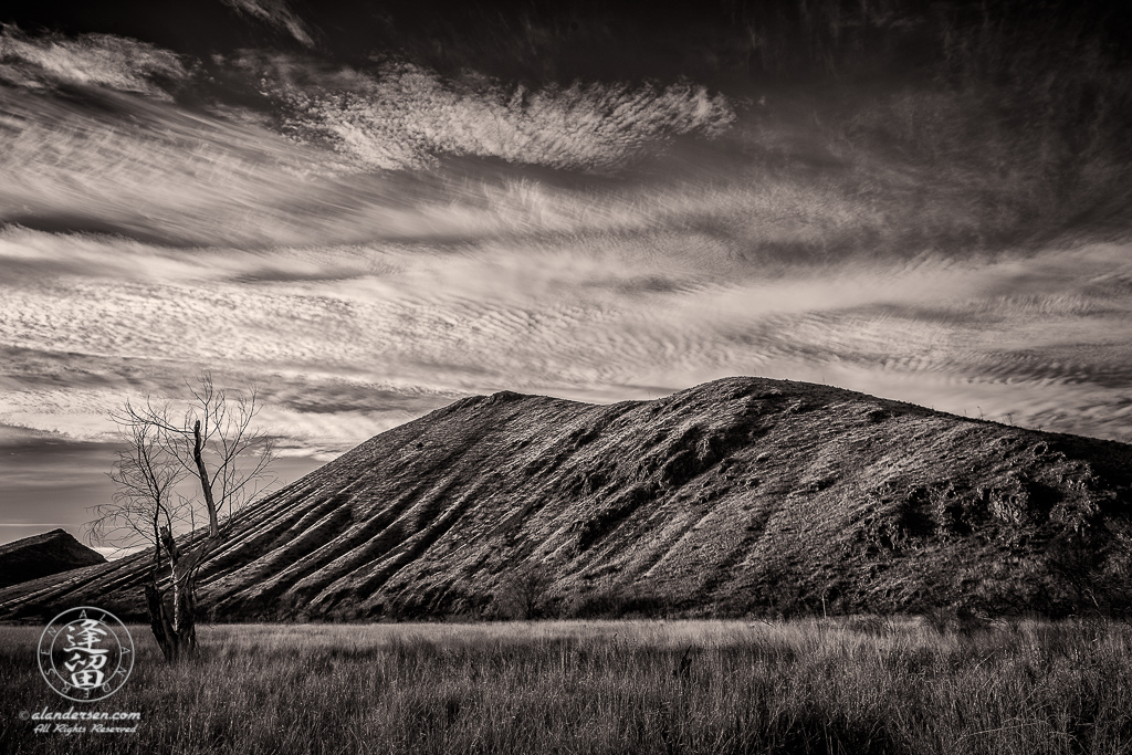 Cirrocumulus clouds looming over eroded hills and grasslands.