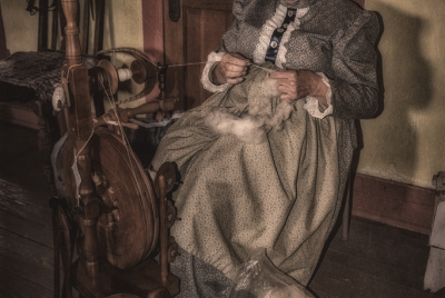 Woman spinning wool in historical dress.