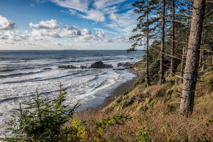 Waves rolling up on narrow shoreline of Washington's Beach 4 beneath a blue sky with white puffy clouds.