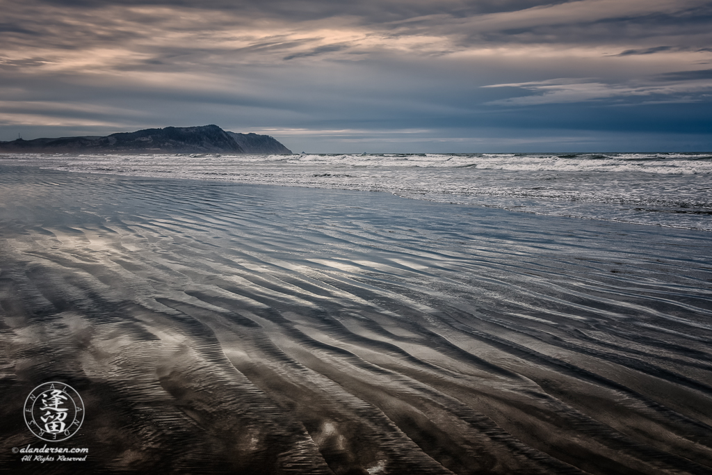 Rippled wet sand reflecting storm clouds from overcast sky at Del Rey Beach State Recreation Site, Oregon.