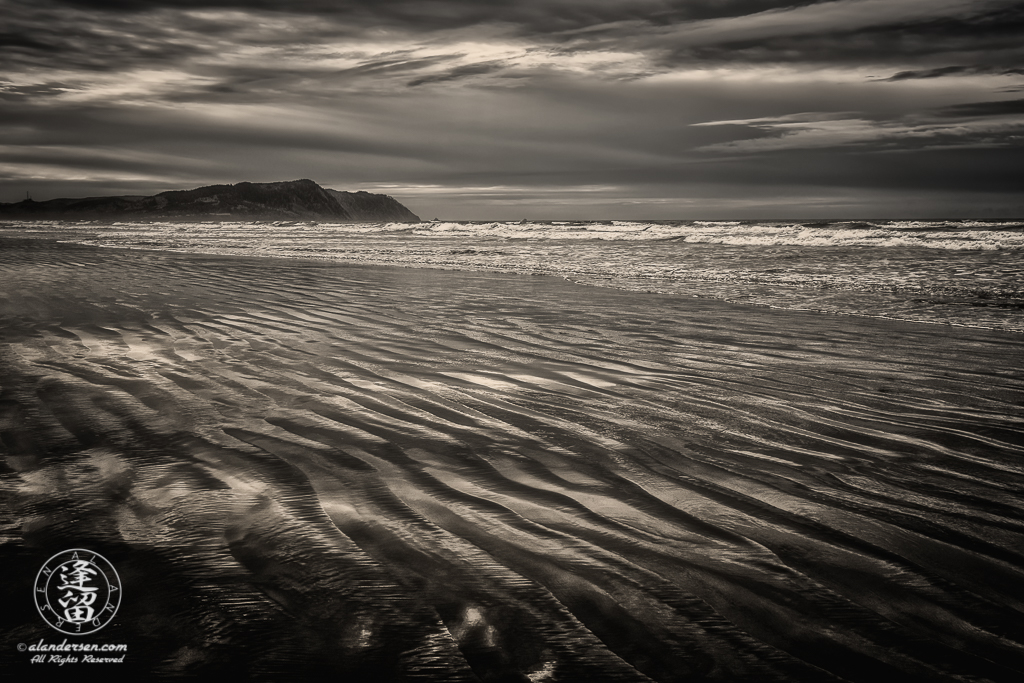 Ripples of wet sand reflect storm clouds in an overcast sky at Del Rey Beach State Recreation Site in Oregon.