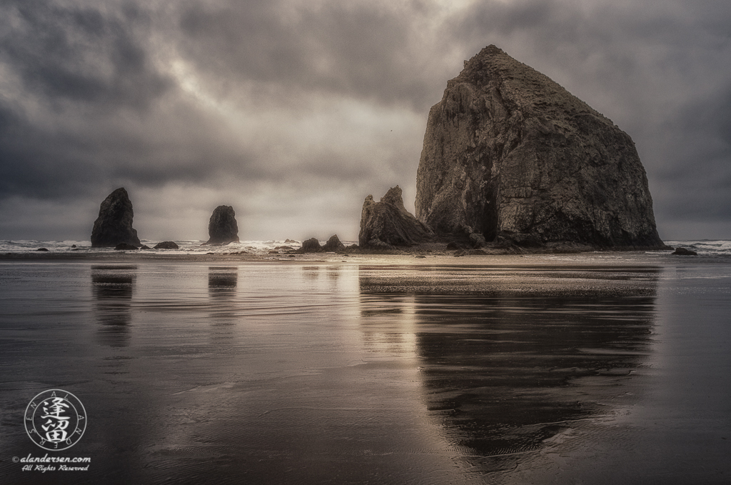 Haystack Rock And The Needles reflected in the wet sand during a stormy wet morning at Cannon Beach in Oregon.