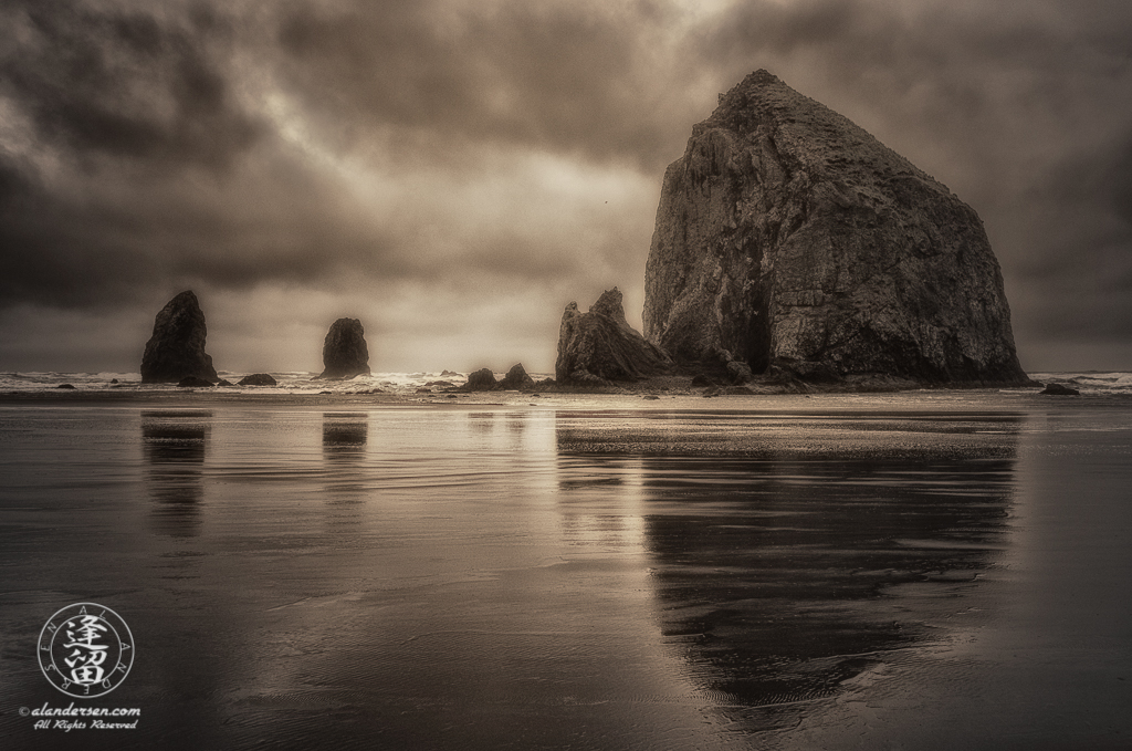 Haystack Rock And The Needles reflected in the wet sand at Oregon's Cannon.