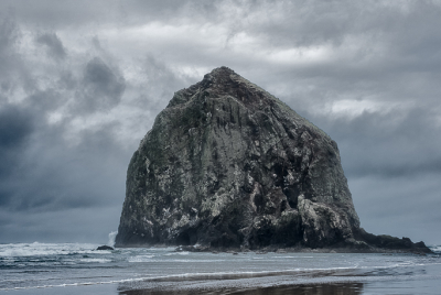 Haystack Rock reflected in the wet sand on cloudy and stormy day.