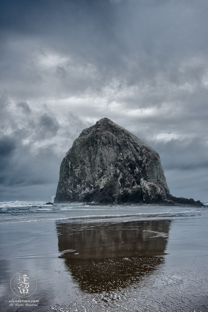 Haystack Rock, at Cannon Beach in Oregon, reflected in the wet sand on a cloudy and stormy day.