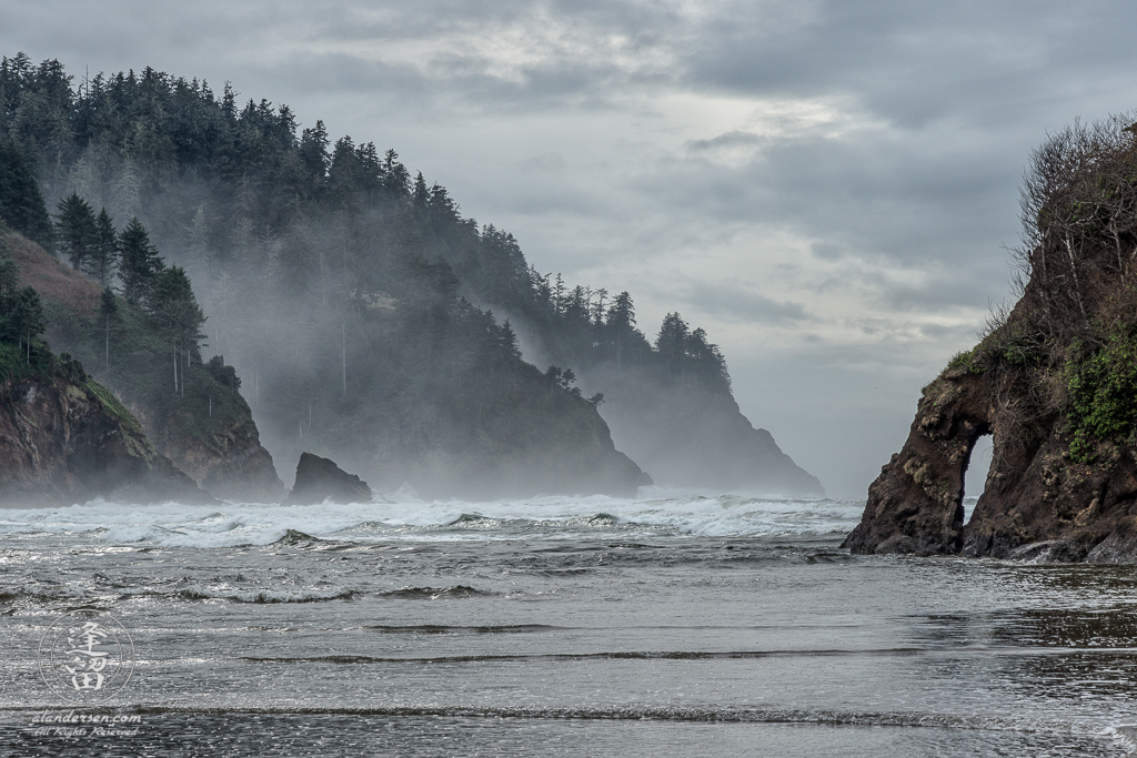 High tide beneath the misty hills on a cloudy day at Proposal Rock in Neskowin, Oregon.