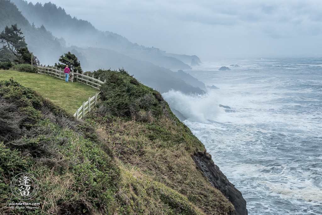 A girl and her dog walk along the top of a fenced off cliff that overlooks the crashing waves of the Pacific Ocean on a stormy day at Rocky Creek State Park in Oregon.