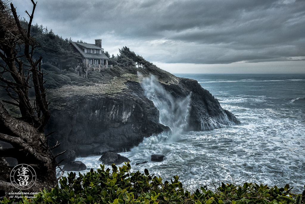 House atop cliffs at Otter Crest Loop during stormy day.