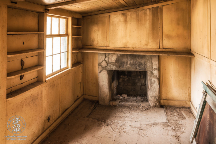 Front room in ranch house at Camp Rucker, Arizona, with wood-paneled walls, fireplace, and built-in book shelves.