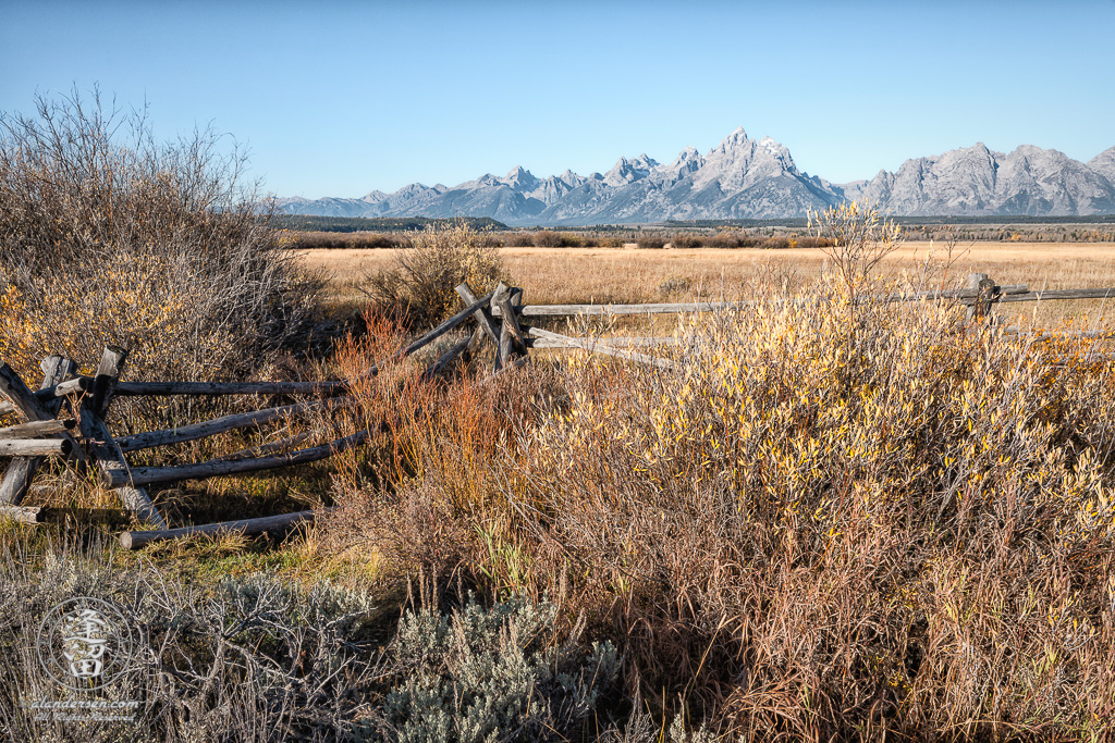 View of Grand Tetons behind the split-rail fence at Cunningham Cabin in Wyoming's Grand Teton National Park.