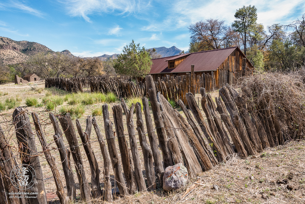 Stockaded barn surrounded by wire-woven log fence at historic Camp Rucker with adobe ruins in the distance.