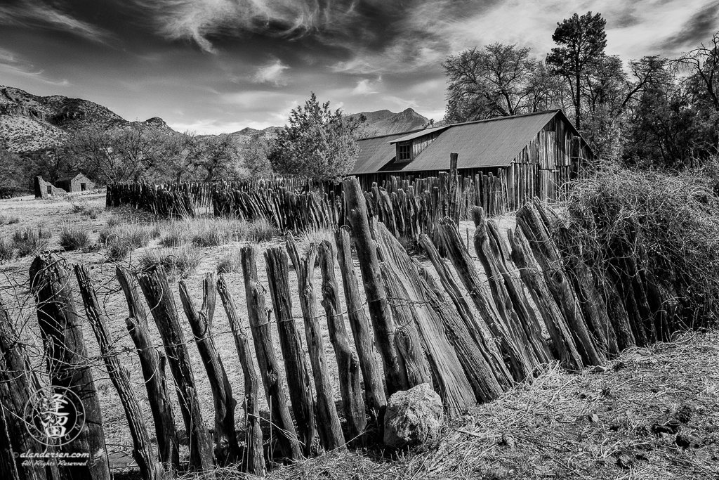 The stockaded barn surrounded by a wire-woven log fence at historic Camp Rucker outside of Douglas, Arizona with the ruins of the old adobe commissary and bakery in the distant background.