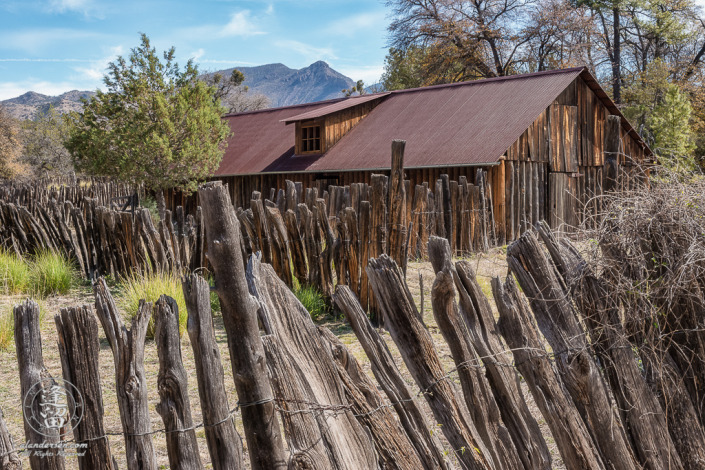 Closeup stockaded barn surrounded by wire-woven log fence at historic Camp Rucker.