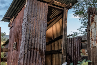 Leaning outhouse made of corrugated tin by Brown Canyon Ranch corrals outside Sierra Vista in Arizona.