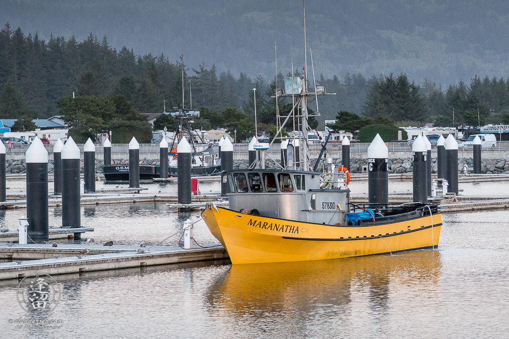 Bright yellow fishing boat Maranatha berthed at Crescent Bay City Marina in Northern California.