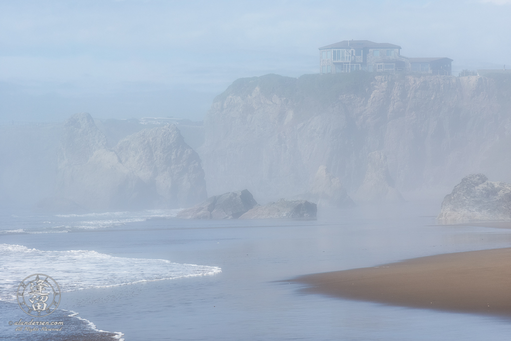 House atop cliffs seen through afternoon mists from beach near Face Rock State Scenic Viewpoint in Bandon Oregon.