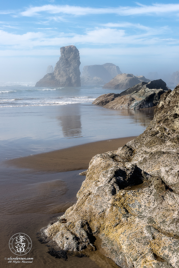 A composition showing various sea stacks at Bandon Beach in Oregon on a misty afternoon.