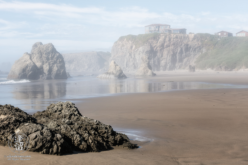 House atop cliffs, seen through the afternoon mists from the beach near Face Rock State Scenic Viewpoint in Bandon, Oregon.