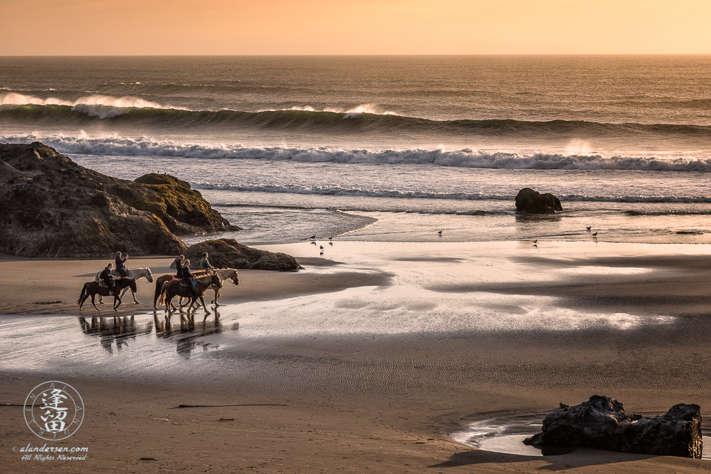 Local horseback riders out enjoying the sunset on Bandon Beach in Oregon.