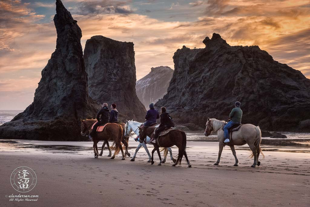 Local horseback riders out enjoying the sunset near Wizard Hat on Bandon Beach in Oregon.
