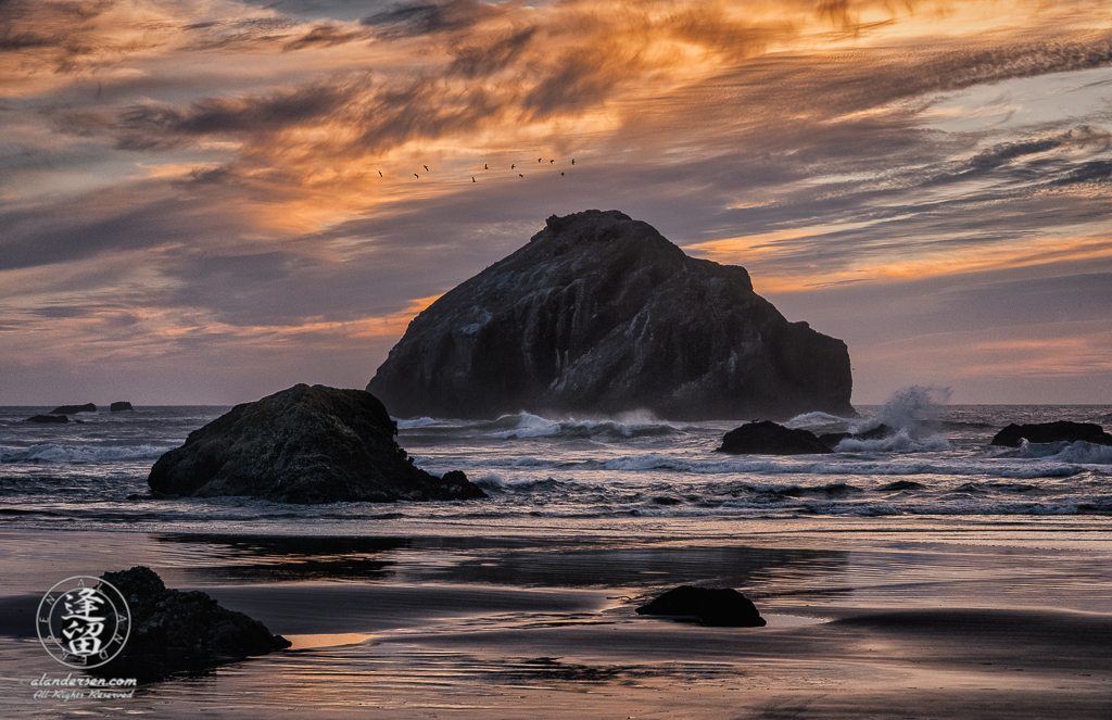 Face Rock in dark silhouette amidst crashing waves during a wonderful sunset at Bandon Beach in Oregon.