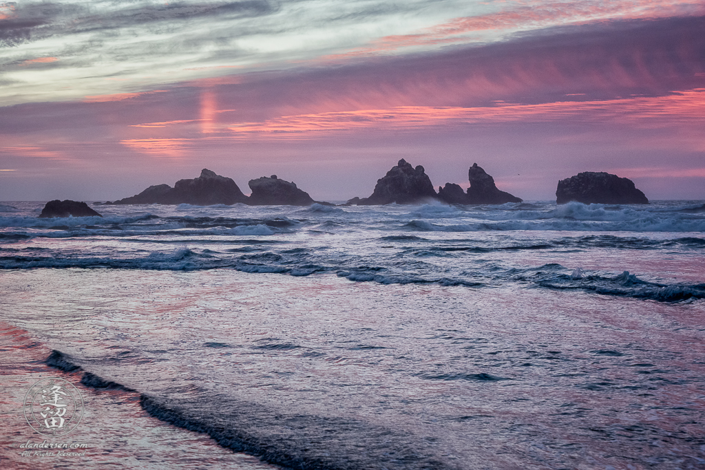Pastel pinks and magentas imbue the seascape during sunset near the Cat & Kittens on Bandon Beach in Oregon.