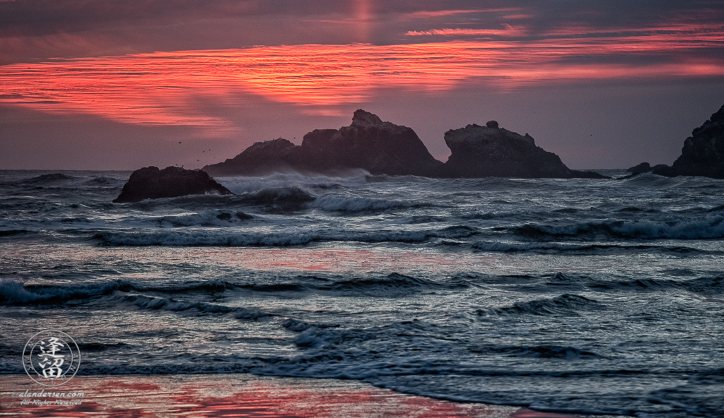 Setting sun casting fiery glow over the Kittens seastacks at Bandon Beach in Oregon.