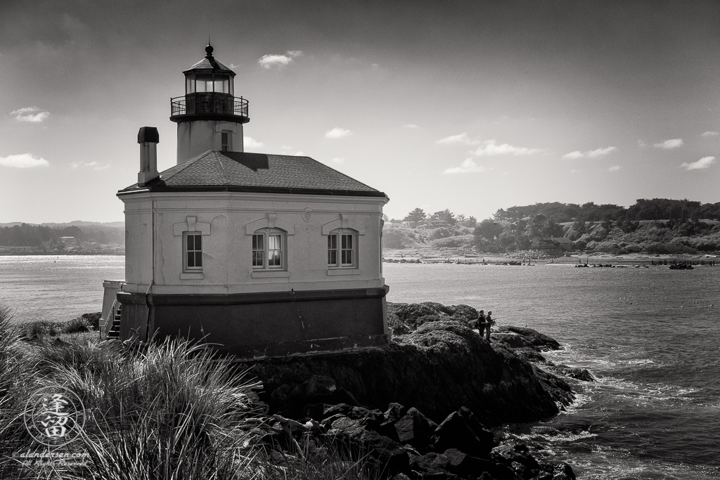 Two men fishing by the Coquille River Lighthouse at the mouth of the Coquille River in Bandon, Oregon.