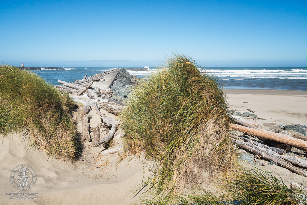 Dunes and grass framing the way out to the North Jetty of the Coquille River at Bandon in Oregon.