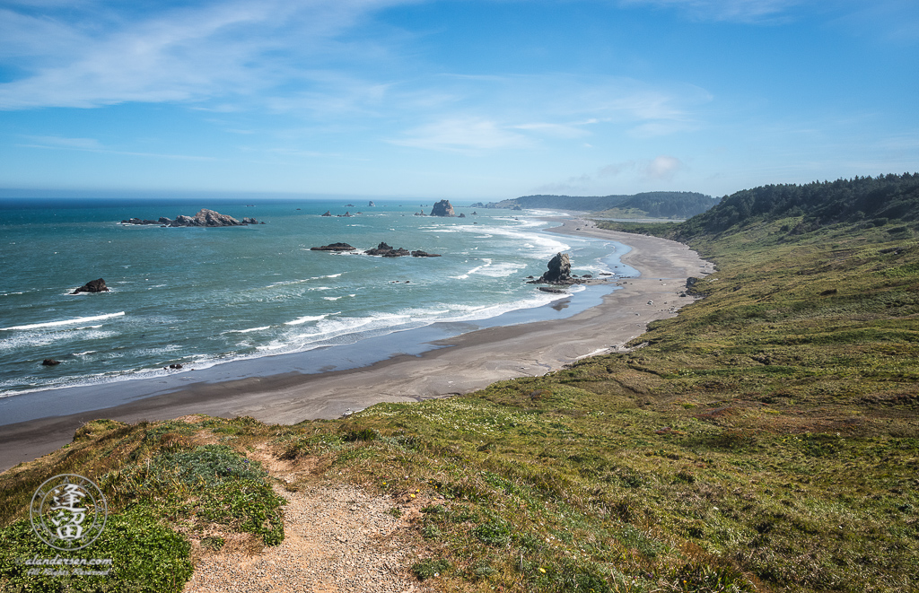 Scenic view of windswept grassy hills and rugged coastline at Cape Blanco State Park in Oregon..